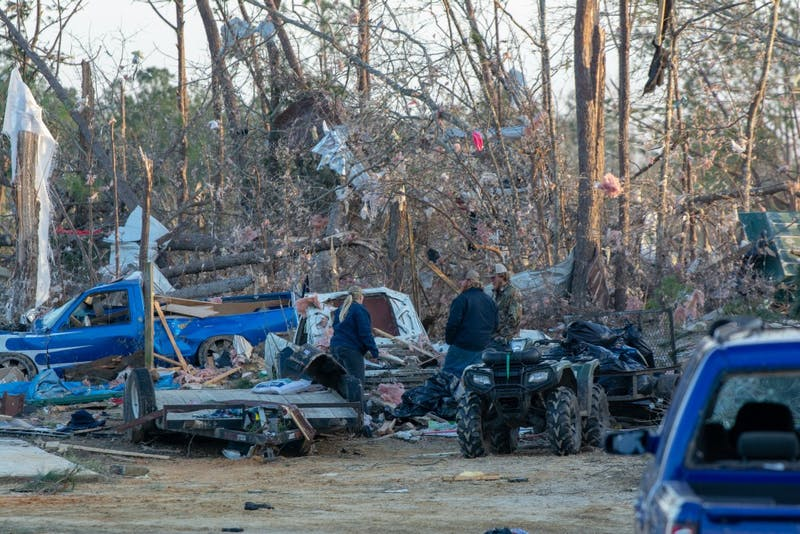 Residents stand together on March 4, 2019, alongside the wreckage caused by a tornado that killed 23 people in Beauregard, Alabama, the previous day.