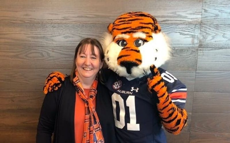 Dee Ford, Auburn fan from Kent, smiles with Aubie the Tiger.