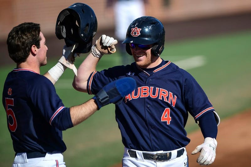 Mar 7, 2020; Auburn, AL, USA; Kason Howell (4) greets third base coach Gabe Gross during the game against Chicago State at Plainsman Park.