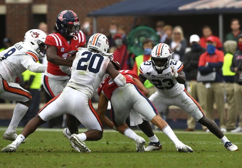 Oct 3, 2020; Oxford, MS, USA; Roger McCreary (23) and Jamien Sherwood (20) get a tackle during the game between Auburn and Ole Miss at Vaught Hemingway Stadium. Mandatory Credit: Todd Van Emst/AU Athletics