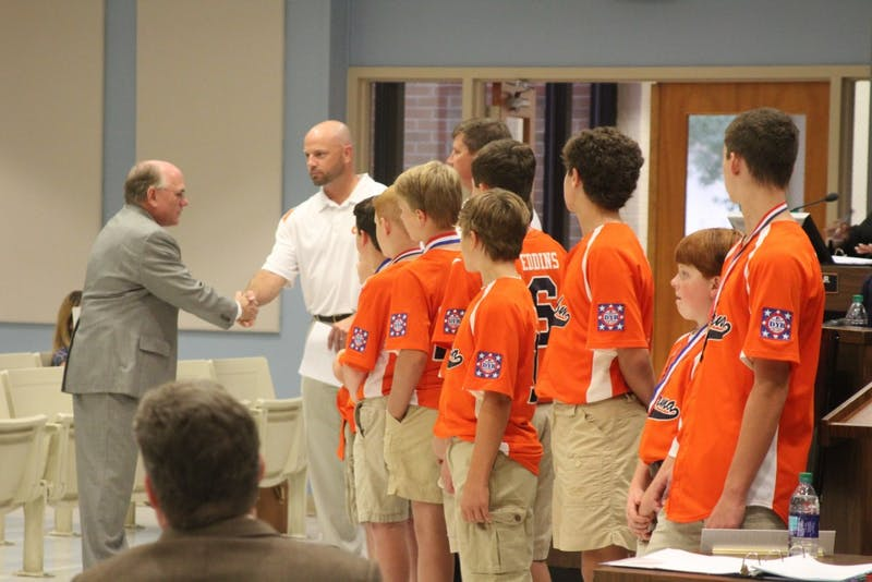 Mayor Bill Ham congratulates theAuburn Orange Dixie Youth baseball team at the city council meeting on Tuesday, Aug. 21, 2018, in Auburn, Ala.