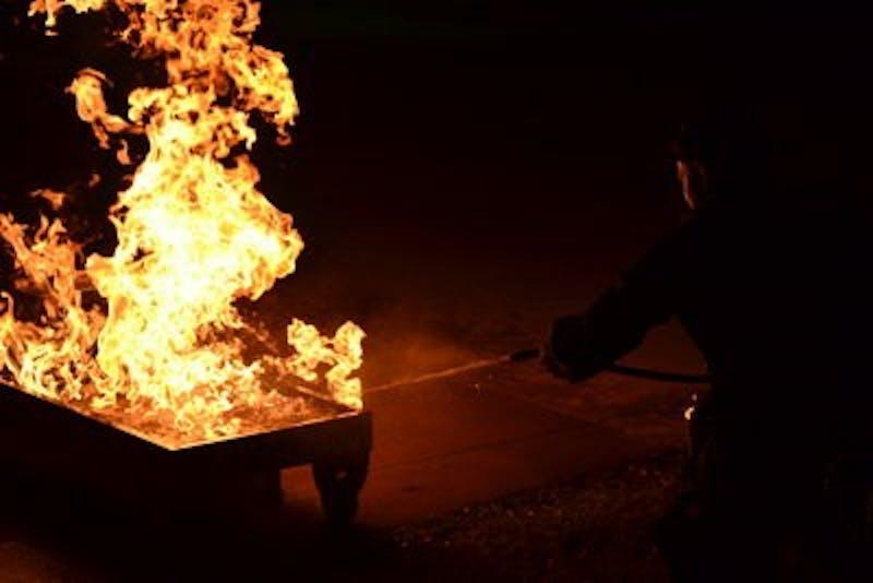 John Matechak and Carl Fox use teamwork to put out a fire.