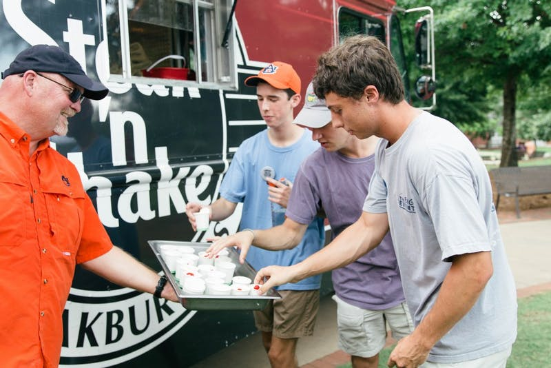 Students pick up mini milkshakes from the Steak 'nShake food truck during the fall's first Family Friday on Aug. 17, 2018, in Auburn, Ala.