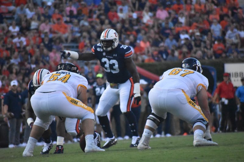 Nate Warnock (54), Nathan Monnin (67) and K.J. Britt (33) prepare for the start of a play during the Auburn v. Kent State game on Saturday, September 14, 2019 in Auburn, AL