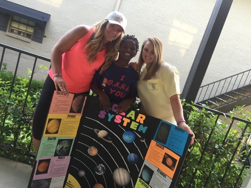 Project Uplift members help a student with her school project.