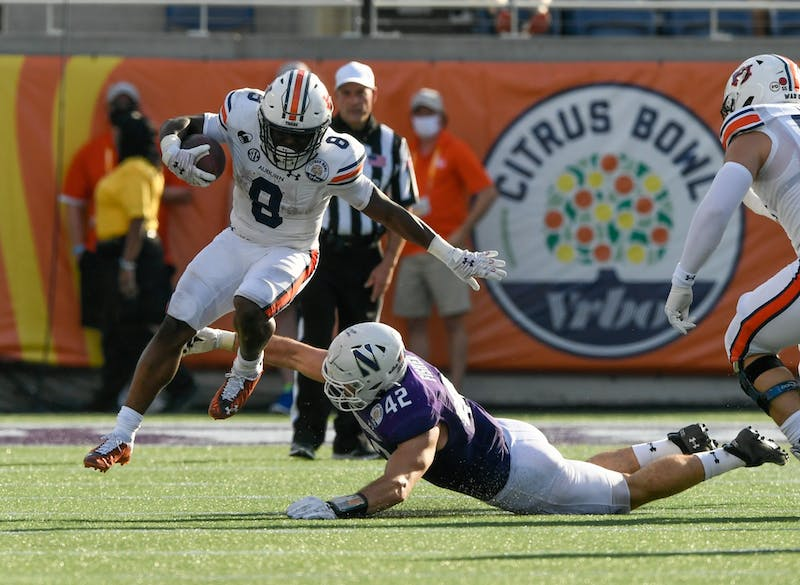 Shaun Shivers (8) avoids the tackle for a big gain during the game between Auburn vs. Northwestern at Orlando on Jan 1, 2021; Orlando FL, USA.