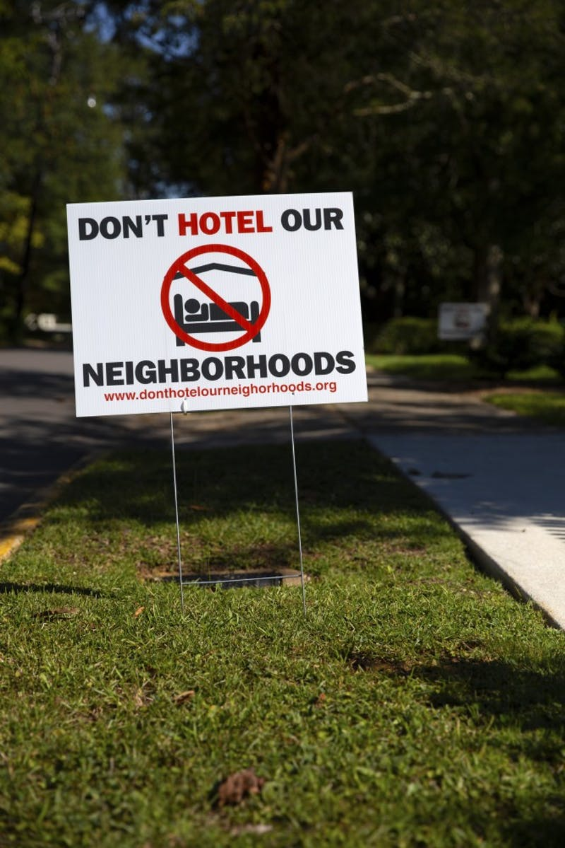 Auburn residents post signs in their yards to speak out against short term rental properties.