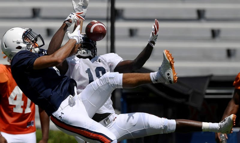 Defender Jayvaughn Myers takes the ball and makes the interception from receiver Anthony Schwartz during scrimmage Thursday.