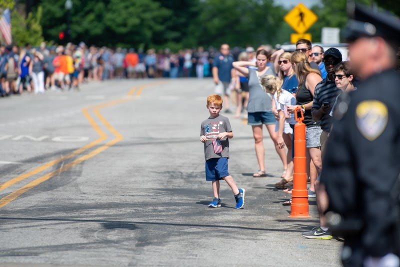 A young boy waits for the Funeral procession of Auburn Police Officer William Buechner on Friday, May 24, 2019, in Auburn, Ala.