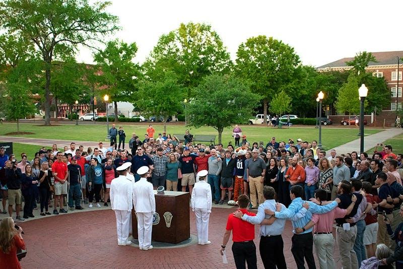 Students, familiesand Auburn University Navy ROTCmemberssing the Alma Materat Ring Night on Thursday, April 19, 2018, in Auburn, Ala.