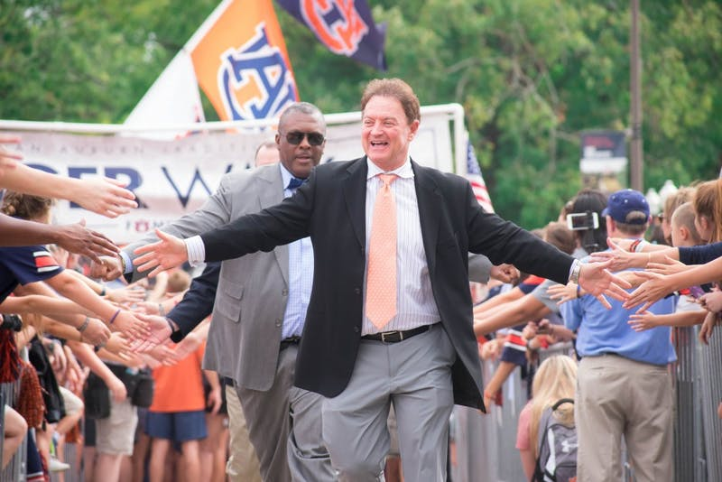 Assistant Coach Greg Brown high-fives fans during Tiger Walk on Saturday, Sept. 30, 2017 in Auburn, Ala.