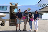 Mac Cook, Shannon Kay, Megan Brown and Caitlyn Miller pose by the Chicken Salad Chick plane.