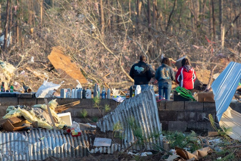 Residents stand together on March 4, 2019, alongside the wreckage of a home completely destroyed by a tornado that killed 23 people in Beauregard, Alabama, the previous day.