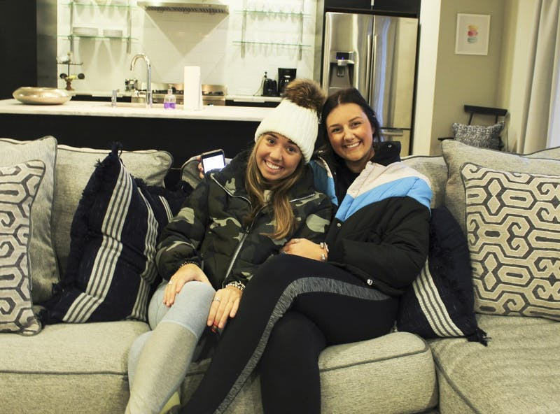 McKenna Moorhead and Sarah Kate Holland pose on their couch in their home in Auburn, Ala. on Jan. 15, 2019.