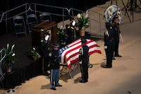 Police Officers drape an American Flag over the casket at the Funeral of Auburn Police Officer William Buechner on Friday, May 24, 2019, in Auburn, Ala.