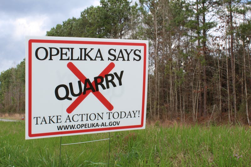 Residents have placed signs around Opelika that state their opposition to a quarry being built near the city.