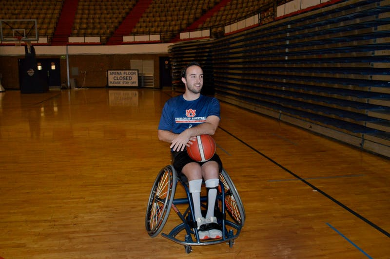 Sam Armas, junior in public administration, sits holding a basketball in the Beard-Eaves-Memorial Coliseum on April 5, 2021.