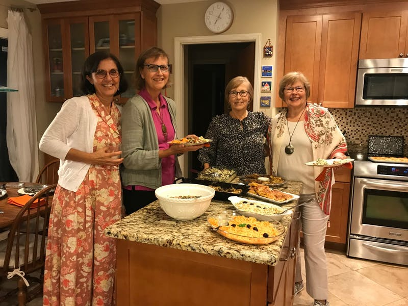 Members of the International Dinner Club pose with a sampling of their meals.