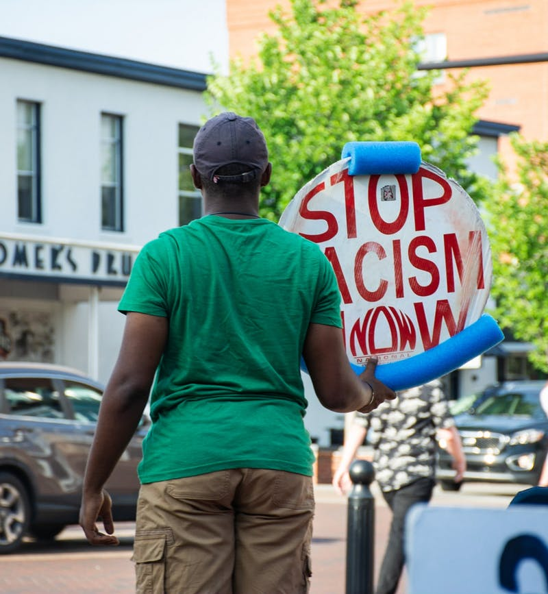 """Damarius Nolan-Watts, one of the original members of the sit-in, holds a sign saying """"STOP RACISM NOW"""" on Toomer's Corner."""
