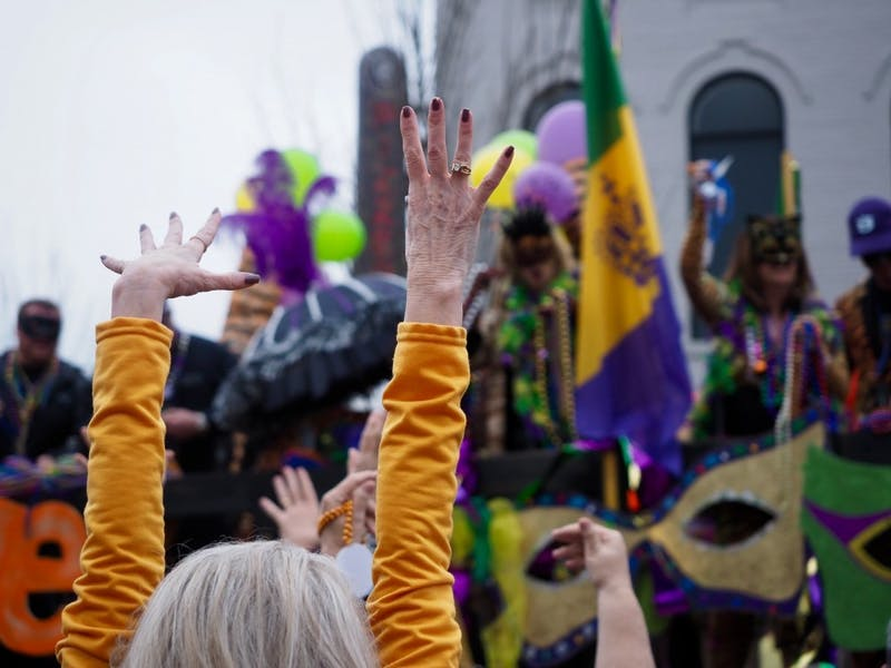 Woman raises her hands to catch beads at the Auburn Mardi Gras Parade on Sat, Mar. 2, 2019 in Auburn, Ala.
