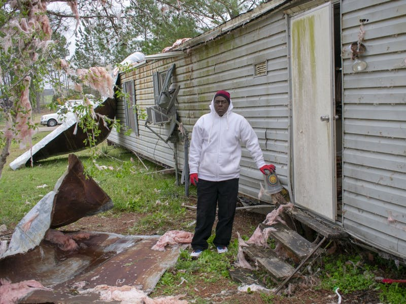 Johnny Washington stands next to the tree stump that held his home in place when a EF-4 tornado passed by on Sunday, March 3, 2019.
