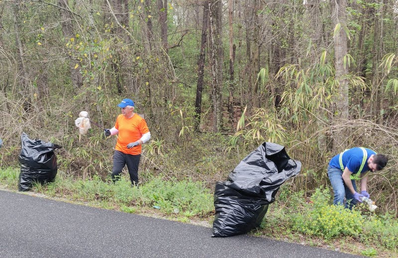Volunteers pick up trash along the road during the last Operation Roadside Cleanup on March 27.