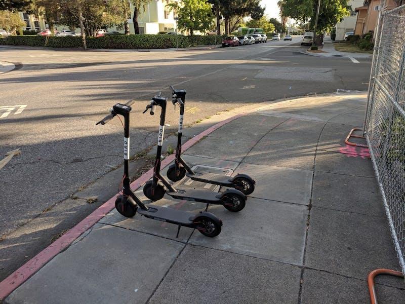 Three bird scooters sit on a sidewalk in San José, California.