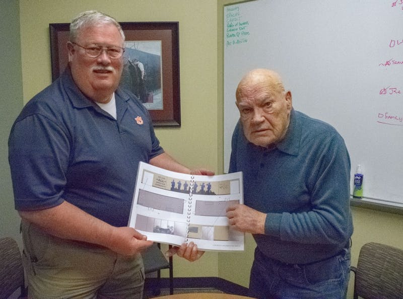 County Commissioner Johnny Lawrence and Command Sergeant Major Bennie G. Adkins hold plans for the new exhibit in the Bennie Adkins Meeting Center.