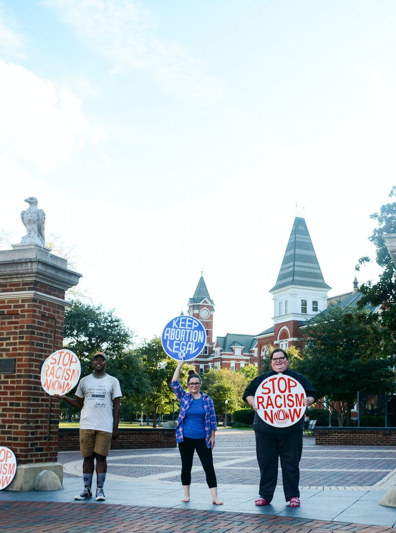Founder, Kelli Thompson, and respective Toomer's sit-in members pose with their signs of protest, 500 days after the initial sit-in.