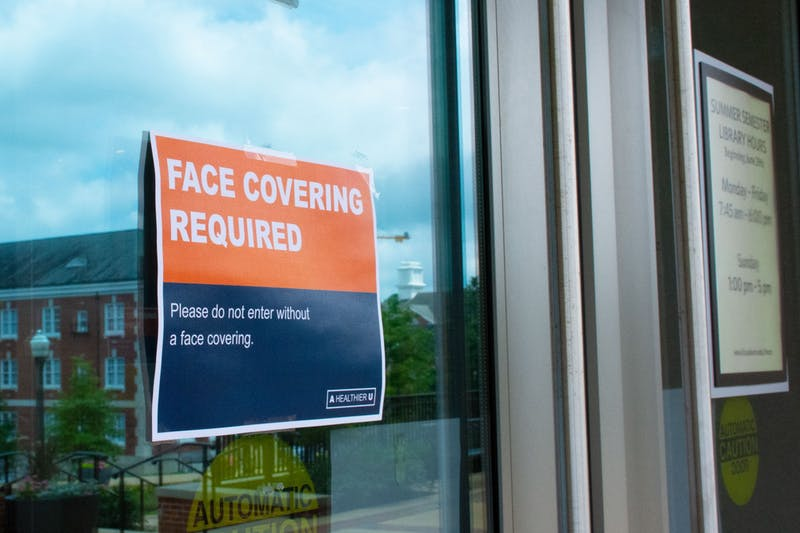 Signs like this have been placed around campus to indicate where masks and social distancing are required.
