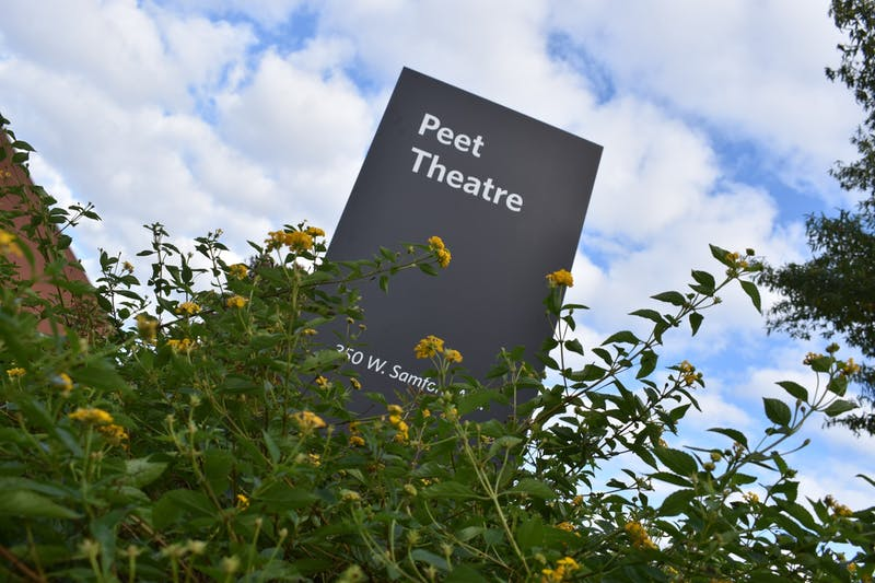 The Peet Theater sign on Auburn University's campus surrounded by wildflowers on Saturday, October 31, 2020.