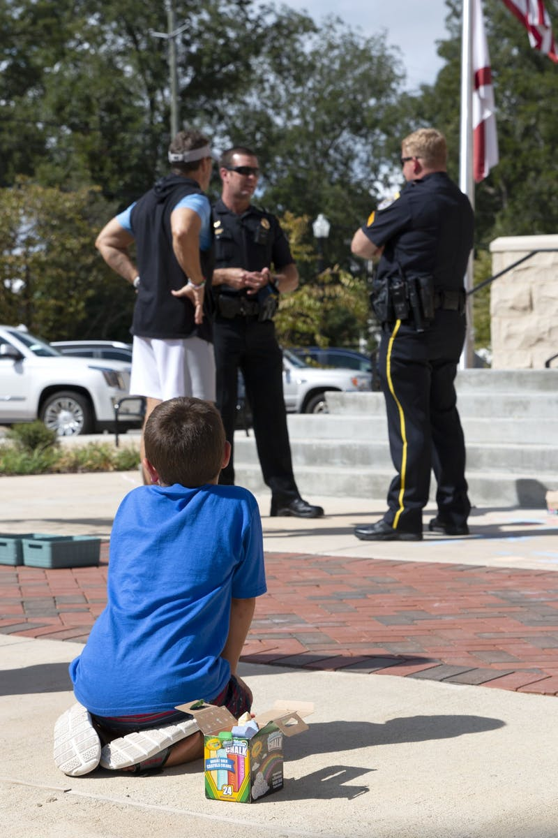 A young boy writes with chalk during the Cookies, Chalk, and Cops event, held outside the Auburn Police Department on September 12th, 2020.