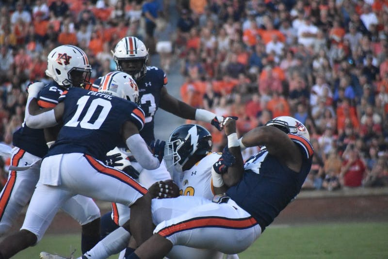 Daniel Thomas (24), Owen Pappoe (10), K.J. Britt (33) and an additional Auburn player tackle a Kent State player for the ball at the Auburn v. Kent State game on Saturday, September 14, 2019 in Auburn, AL.
