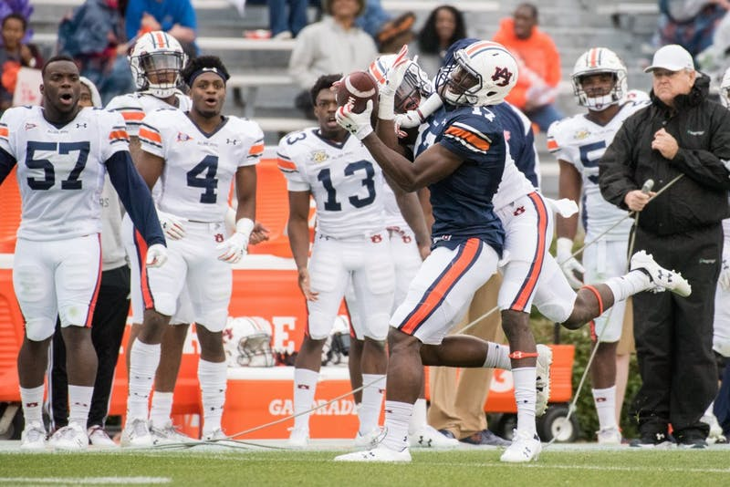 Marquis McClain (17) hauls in a catch with a defender over his shoulder during Auburn's A-Day game on Saturday, April 7, 2018, in Auburn, Ala.