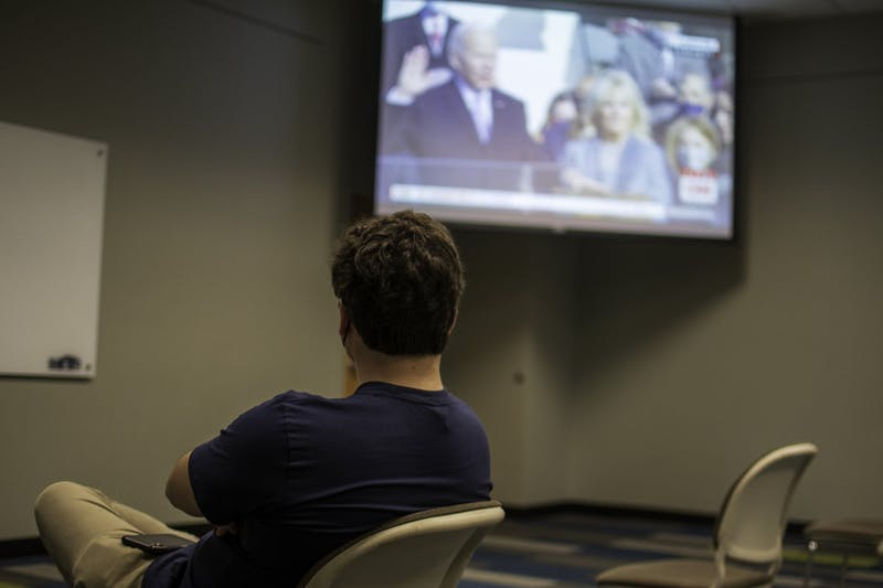 A member of the Auburn College Democrats watches the Inauguration of President Joeseph Biden, on Wed, Jan. 20, 2021, in Auburn, Ala.