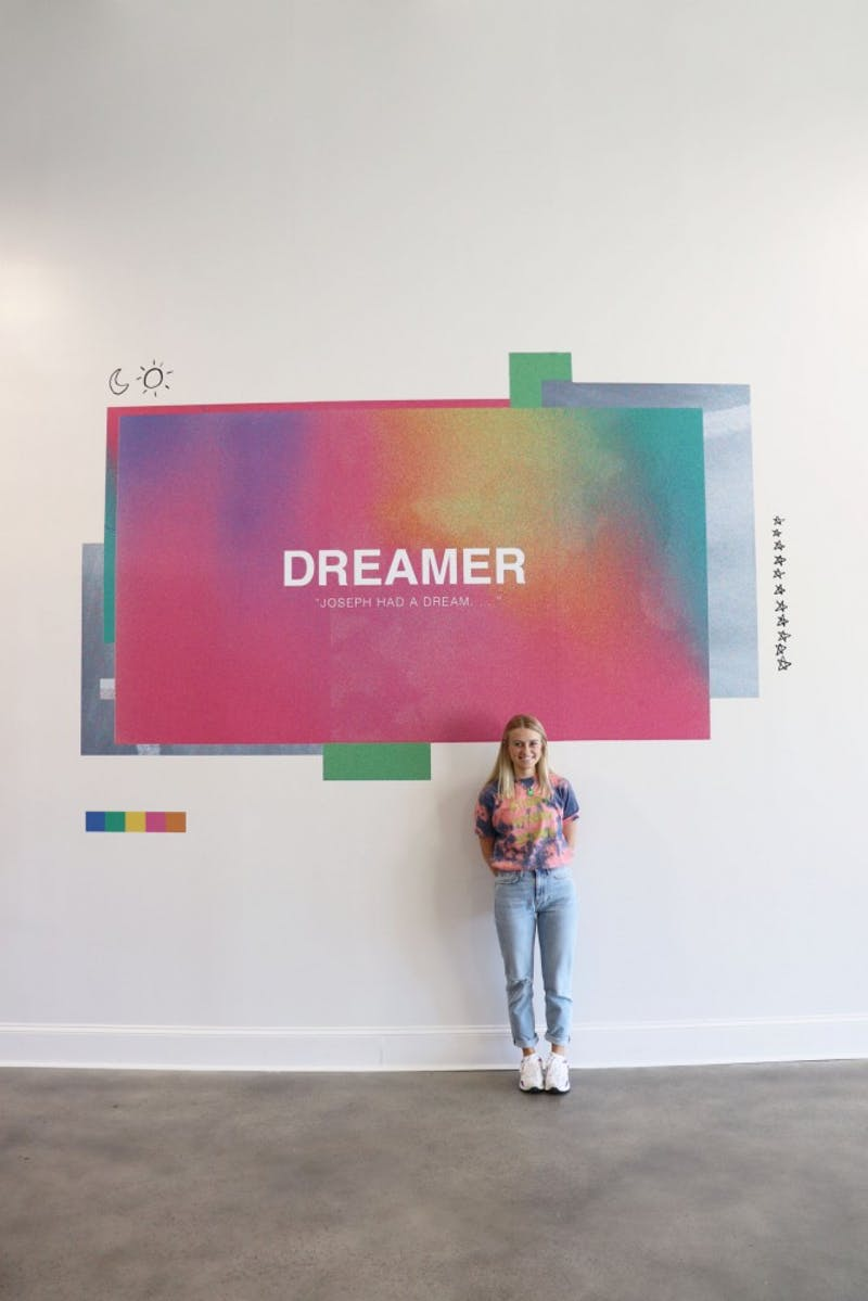 Graphic designer Megan Kesting featured standing by her artwork