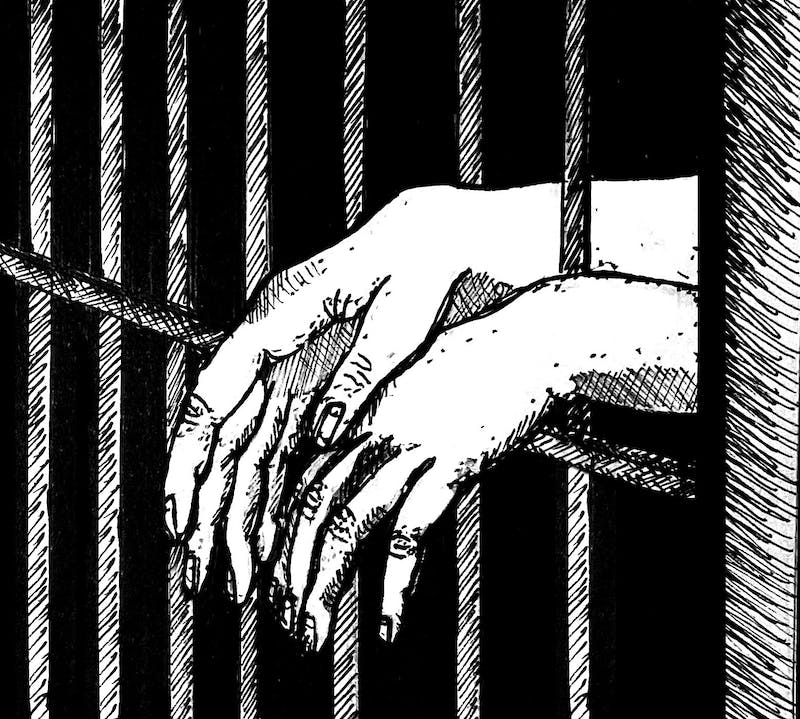 Hands dangling out of the bars of a prison cell.