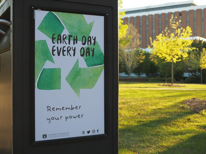 "Earth Day posters placed on trash cans across campus remind students to recycle and ""Remember their power,"" Auburn, AL 2021."