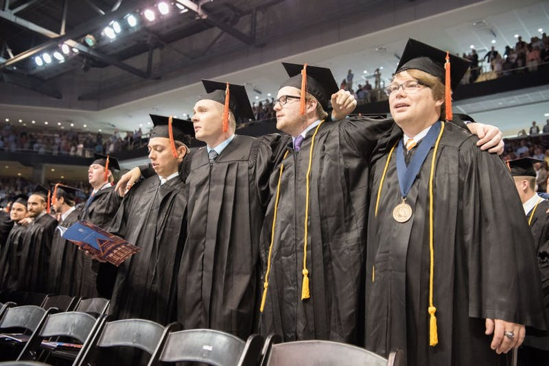 Graduates link arms and sing the Alma Mater during Auburn University commencement exercises in Auburn Arena in Auburn, Ala., on Saturday, May 5, 2018.