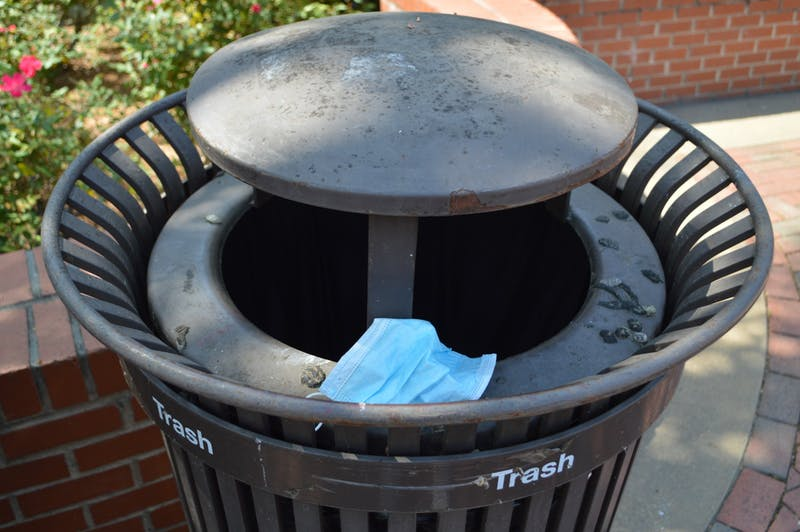 Mask pictured in a trash can on Auburn Universities campus on Apr. 7, 2021, in Auburn, Ala.