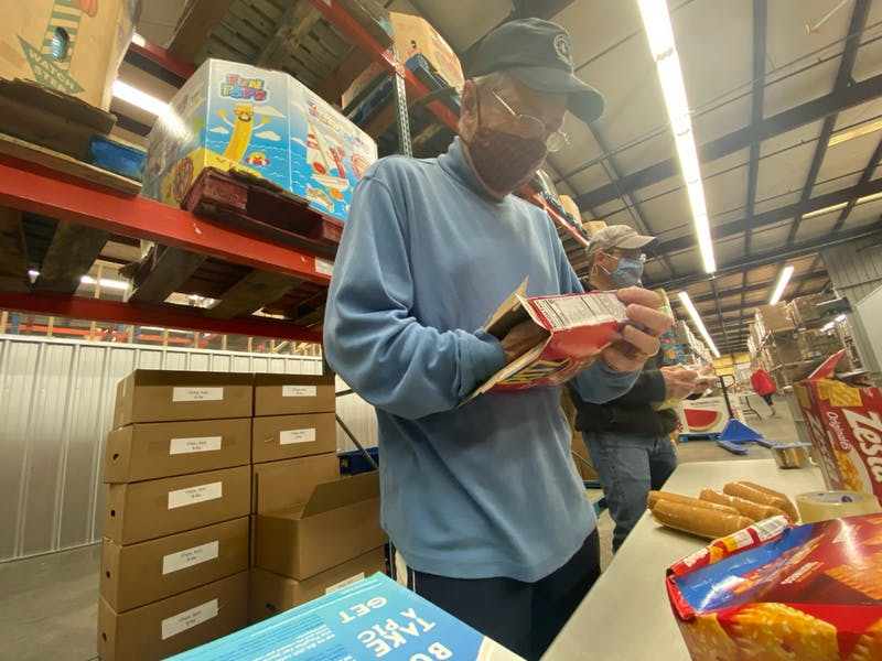 James Newton removes rolls of crackers from a box at the East Alabama Food Bank in Auburn, Ala.