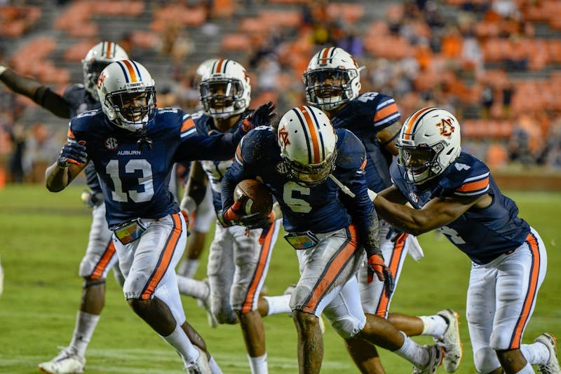 Javaris Davis (13), Noah Igbinoghene (4) celebrate with Christian Tutt (6) after he made an interception during Auburn Football vs. Southern Miss on Saturday, Sept. 29, 2018, in Auburn, Ala.