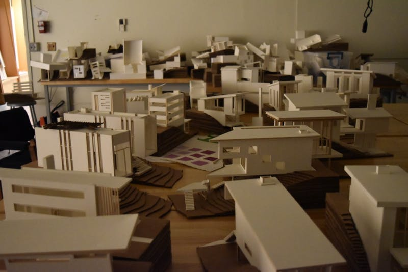 Projects from a summer of architecture scattered around the room.