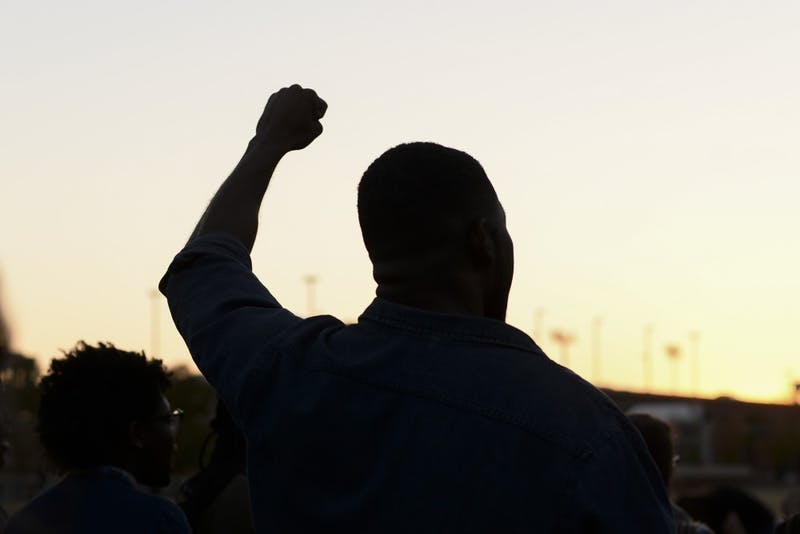 A student holds his fist up during a chant during a sit-in protest at the Student Center Greenspace.