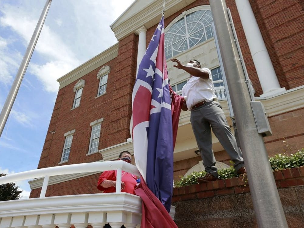 City of Tupelo Community Outreach Coordinator Marcus Gary takes down the Mississippi state flag that flew over the City Hall of Tupelo one last time June 29, 2020. Mississippi is retiring the last state flag in the U.S. that includes the Confederate battle emblem. (Thomas Wells/The Northeast Mississippi Daily Journal via AP, File)