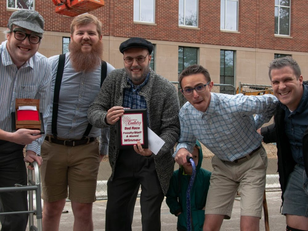 Housing and Residence Life faculty members pose with their plaque after competing in the Bed Race, an annual Homecoming event Oct. 19, 2018, on Riverside Ave. The team earned their title for having the fastest time in the faculty/staff and alumni category. Madeline Grosh,DN