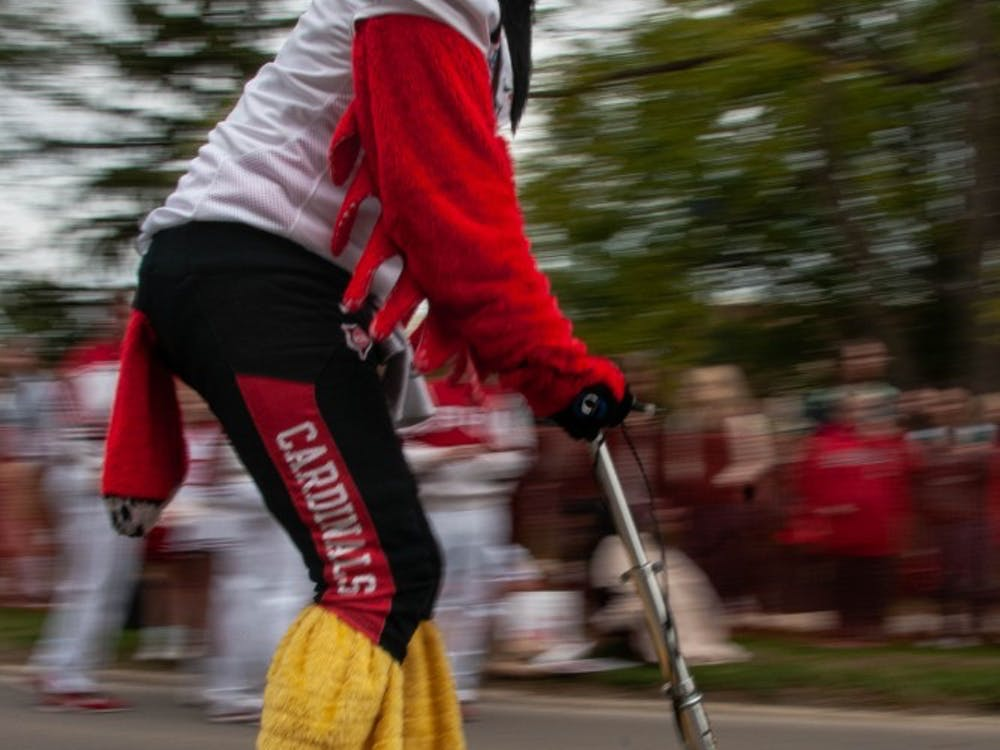 Charlie Cardinal races down Riverside Ave. on a scooter during downtime inbetween races at the annual Homecoming event, Bed Race Oct. 19, 2018, on Ball State's campus. Charlie was the final referee during the races Friday afternoon. Madeline Grosh,DN