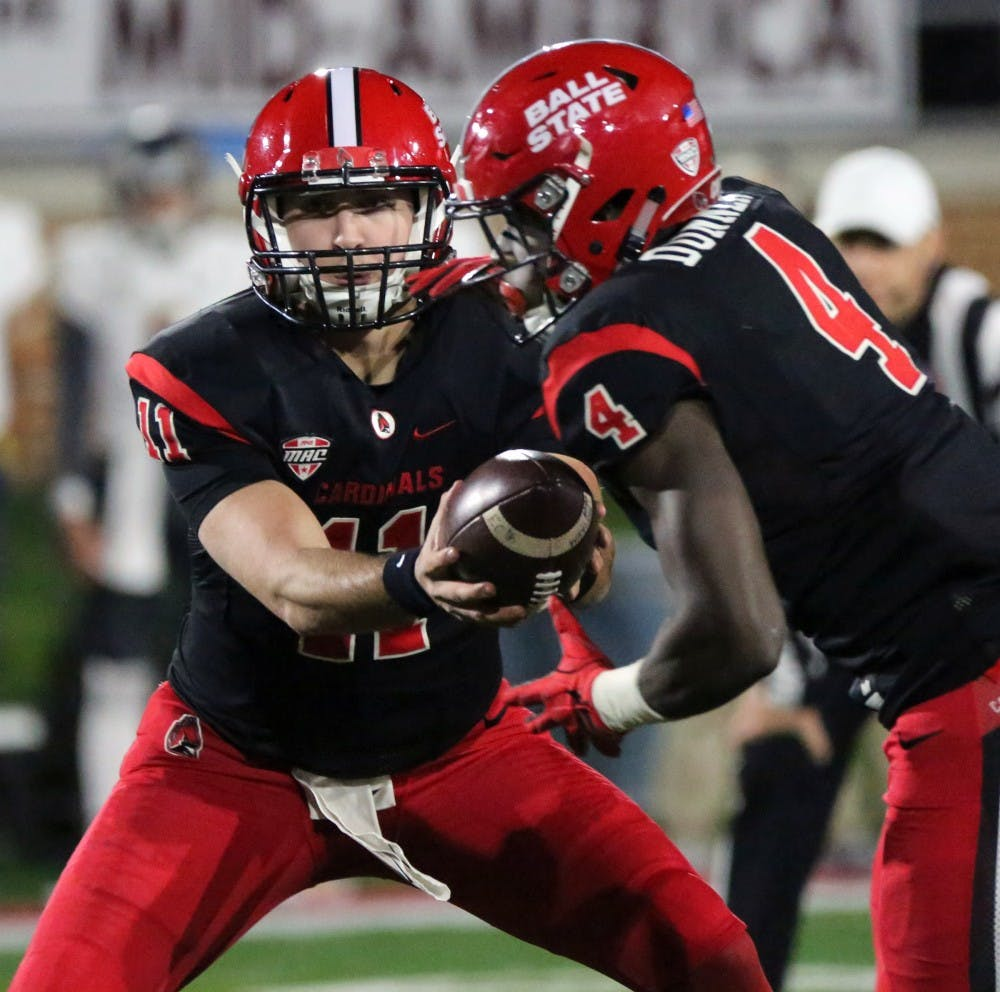 Redshirt freshman quarterback Drew Plitt hands off the ball to sophomore running back Malik Dunner during the Cardinals' game against Toledo on Oct. 26 at Scheumann Stadium. Ball State lost 58-17. Paige Grider, DN File