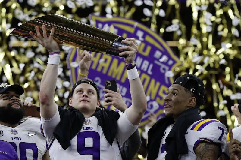 LSU quarterback Joe Burrow holds the trophy as safety Grant Delpit looks on after a NCAA College Football Playoff national championship game against Clemson, Jan. 13, 2020, in New Orleans. LSU won 42-25. (AP Photo/Sue Ogrocki)
