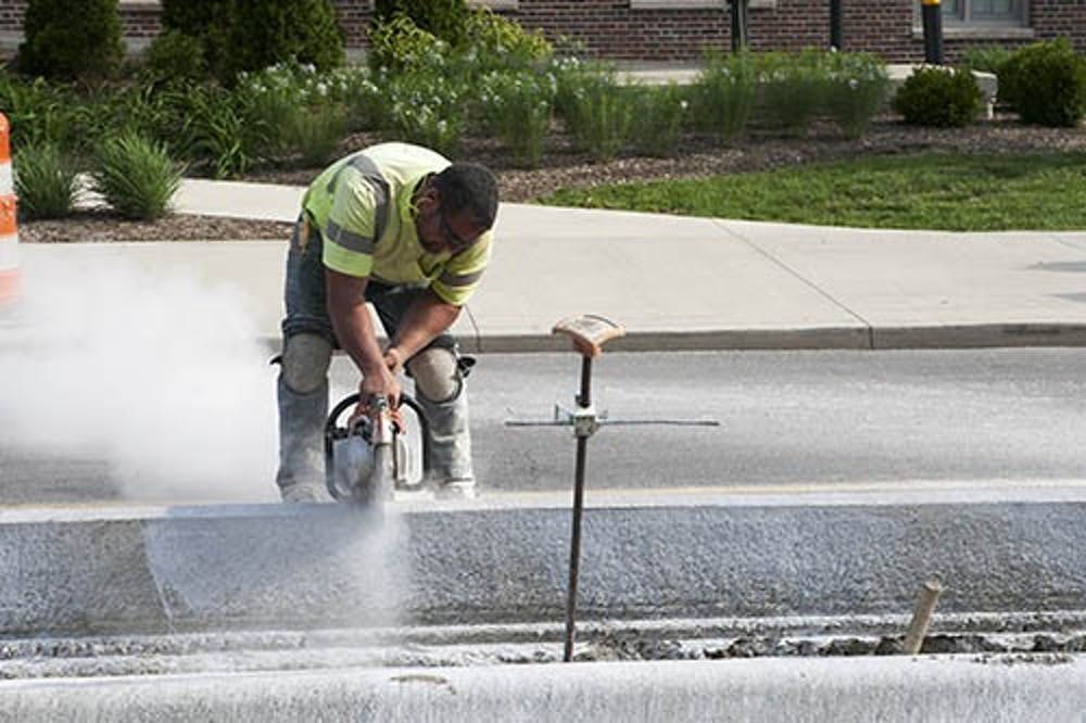 A construction worker uses a saw to create a drainage line in the curb on Riverside Avenue. The construction project's aim is to expand the median and add more crosswalks and ramps on the section of the street. DN PHOTO JORDAN HUFFER